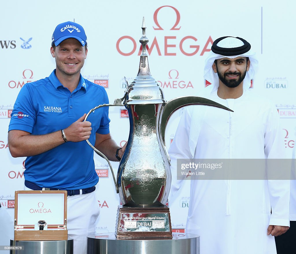 Danny Willett of England is presented with the trophy by Sheikh Mansoor bin Mohammed bin Rashid al-Maktoum after the final round of the Omega Dubai Desert Classic at the Emirates Golf Club on February 7, 2016 in Dubai, United Arab Emirates.