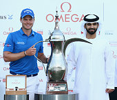 Danny Willett of England is presented with the trophy by Sheikh Mansoor bin Mohammed bin Rashid alMaktoum after the final round of the Omega Dubai...