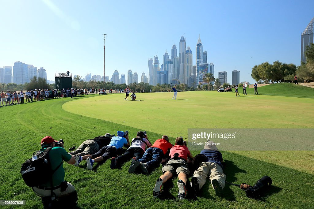 Danny Willett of England plays his second shot at the par 5, 15th hole watched by a group of 'prone' photographers during the final round of the 2016 Omega Dubai Desert Classic on the Majlis Course at the Emirates Golf Club on February 7, 2016 in Dubai, United Arab Emirates.