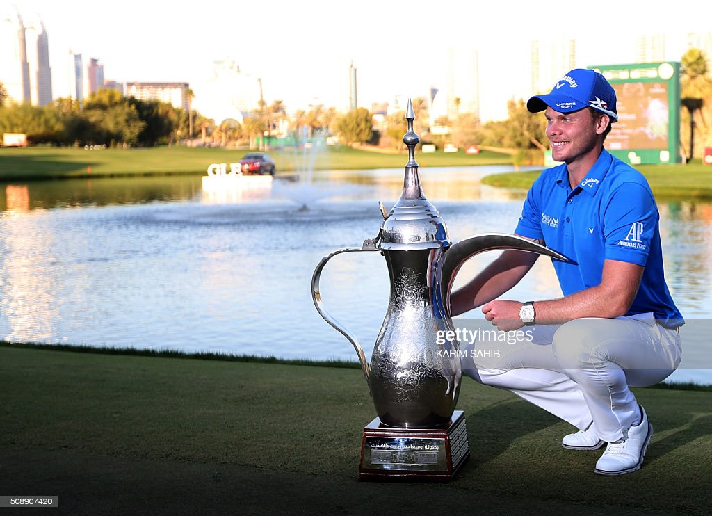 Danny Willett of England poses for a picture with the winners trophy after winning the 2016 Dubai Desert Classic at the Emirates Golf Club in Dubai on February 7, 2016. Willett made a pressure-packed 15-feet birdie putt on the 18th hole to win the Dubai Desert Classic by one shot over Englands Andy Sullivan and Spains Rafael Cabrera-Bello. SAHIB