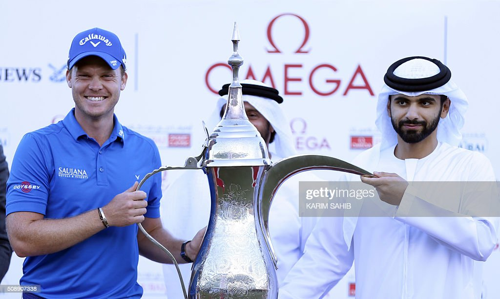 Danny Willett of England poses with Sheikh Mansour bin Mohammed bin Rashid al-Maktoum after his victory in the 2016 Dubai Desert Classic at the Emirates Golf Club in Dubai on February 7, 2016. / AFP / KARIM SAHIB