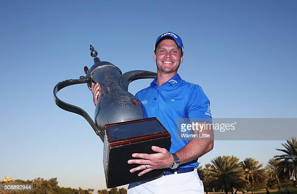 Danny Willett of England poses with the trophy after his victory in the Omega Dubai Desert Classic at the Emirates Golf Club on February 7 2016 in...