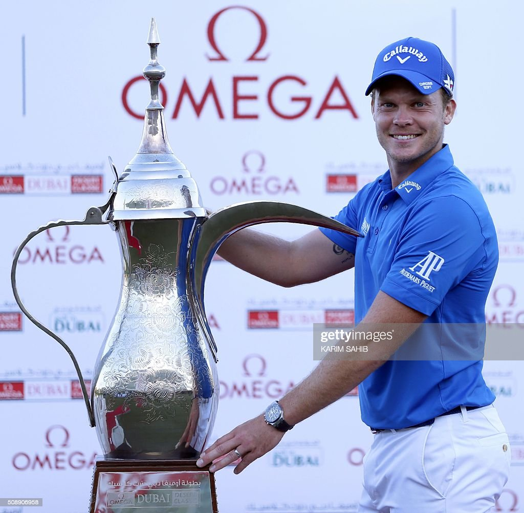 Danny Willett of England poses with the trophy after his victory in the 2016 Dubai Desert Classic at the Emirates Golf Club in Dubai on February 7, 2016. / AFP / KARIM SAHIB