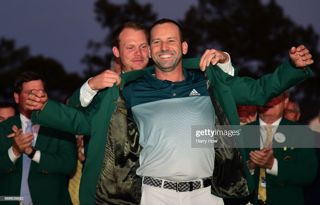 Danny Willett of England presents Sergio Garcia of Spain with the Green Jacket after Garcia won in a playoff during the final round of the 2017 Masters Tournament at Augusta National Golf Club on April 9, 2017 in Augusta, Georgia.