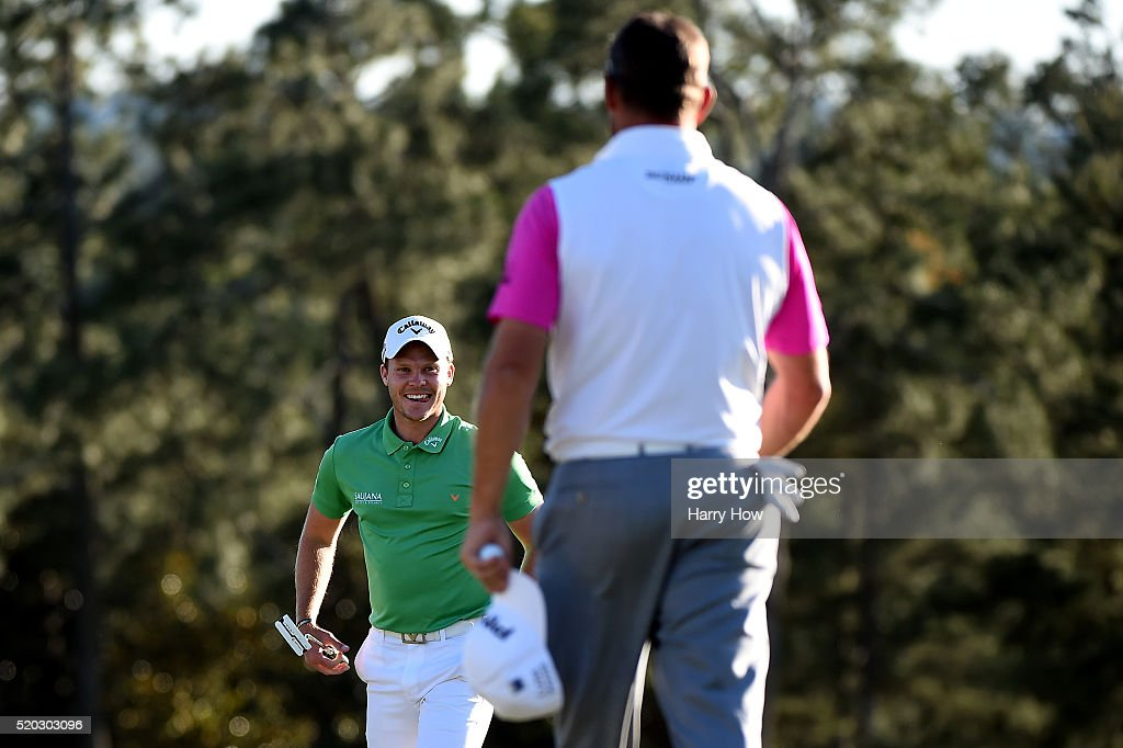 Danny Willett of England reacts as he and Lee Westwood of England finish on the 18th green during the final round of the 2016 Masters Tournament at...