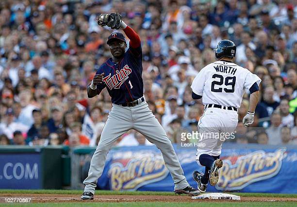 Danny Worth of the Detroit Tigers beats the throw to Orlando Hudson of the Minnesota Twins as he covers first base during the second inning of the...
