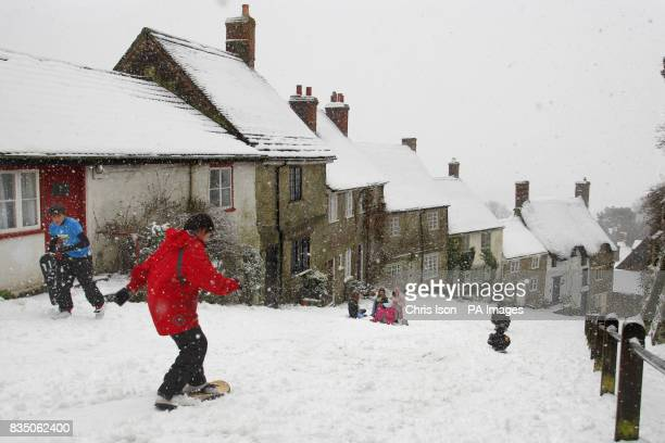 Danny Wyman heads down the iconic Gold Hill in Shaftesbury Dorset on his snowboard after it has snowed everyday this week in the area
