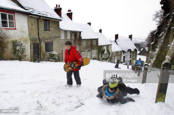 Danny Wyman walks up the iconic Gold Hill in Shaftesbury Dorset where it has snowed everyday this week with his snowboard as two friends sledge past...