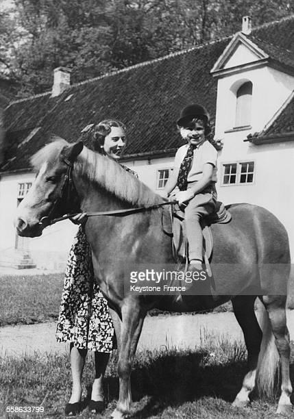 Dans la cour du Palais de Fredensborg la Reine Ingrid souhaite une bonne promenade a la petite AnneMarie parfaitement a l aise sur son cheval le 21...