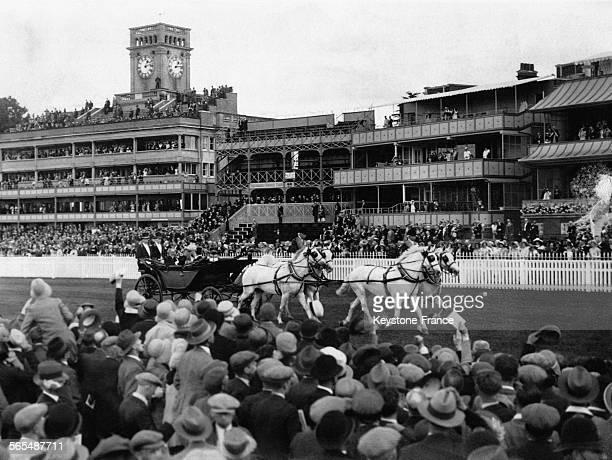 Dans leur calèche tirée par quatre chevaux blancs le Roi George V et la Reine Mary sont acclamés par les spectateurs venus assister à la course...