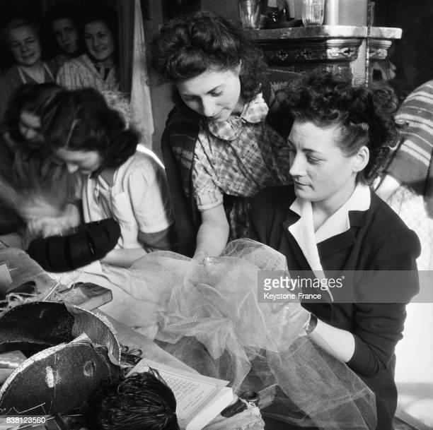 Dans un atelier de couture une jeune fille travaille activement à son chapeau à Paris France en 1946