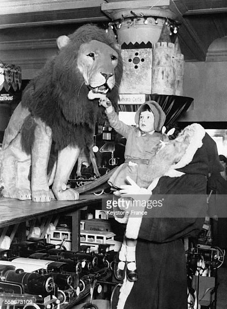 Dans un magasin de jouets un homme déguisé en Père Noël porte dans ses bras une petite fille très intéressée par une grande peluche en forme de lion...
