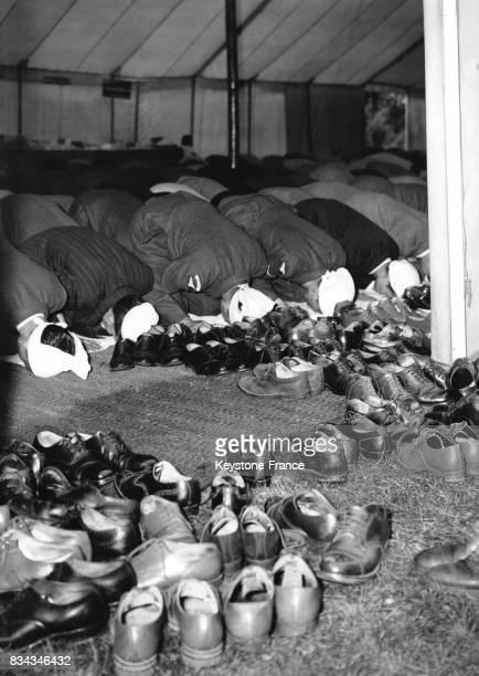 Dans une mosquée les hommes prient et le chaussures sont laissées à l'extérieur du lieu de culte à Londres RoyaumUni le 12 septembre 1951