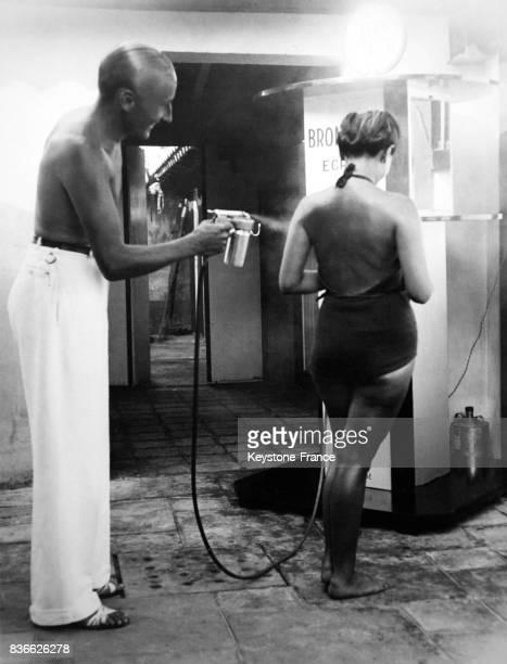 Dans une station de bronzage un homme utilise le pistolet à bronzer sur le dos d'une jeune femme