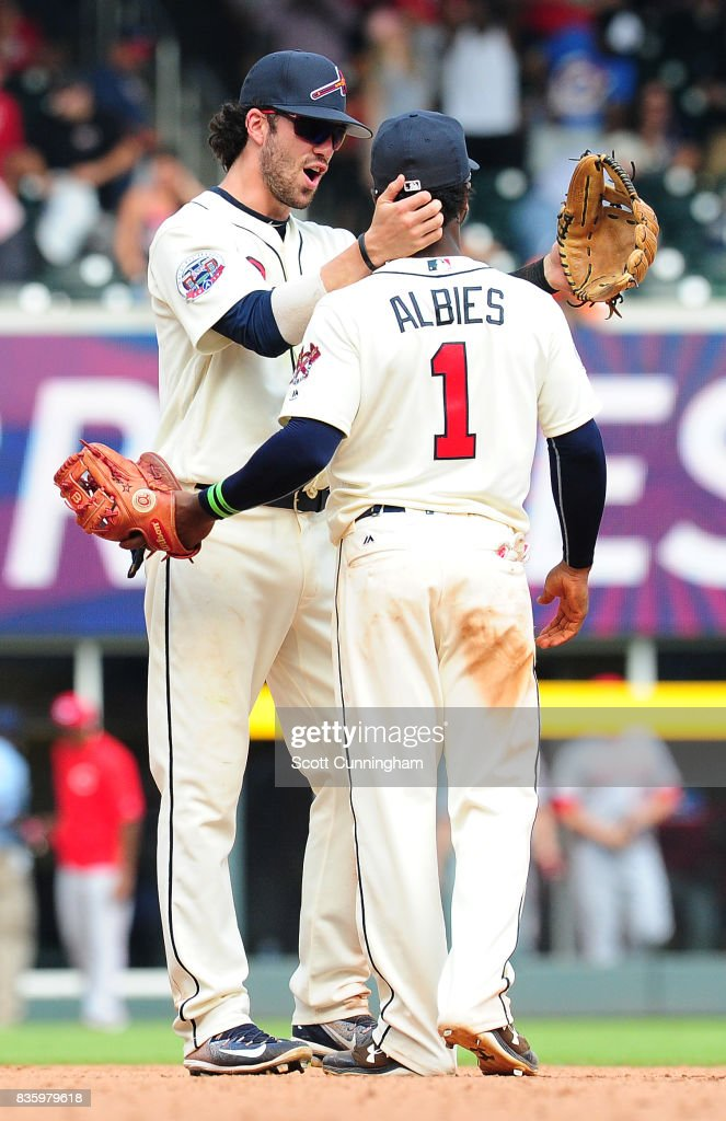 Dansby Swanson #7 and Ozzie Albies #1 of the Atlanta Braves celebrate after the game against the Cincinnati Reds at SunTrust Park on August 20, 2017 in Atlanta, Georgia.