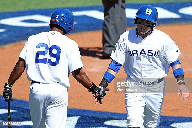 Dante Bichette Jr of Team Brazil is greeted by teammate Juan Carlos Muniz after scoring a run during Game 1 of the 2016 World Baseball Classic...