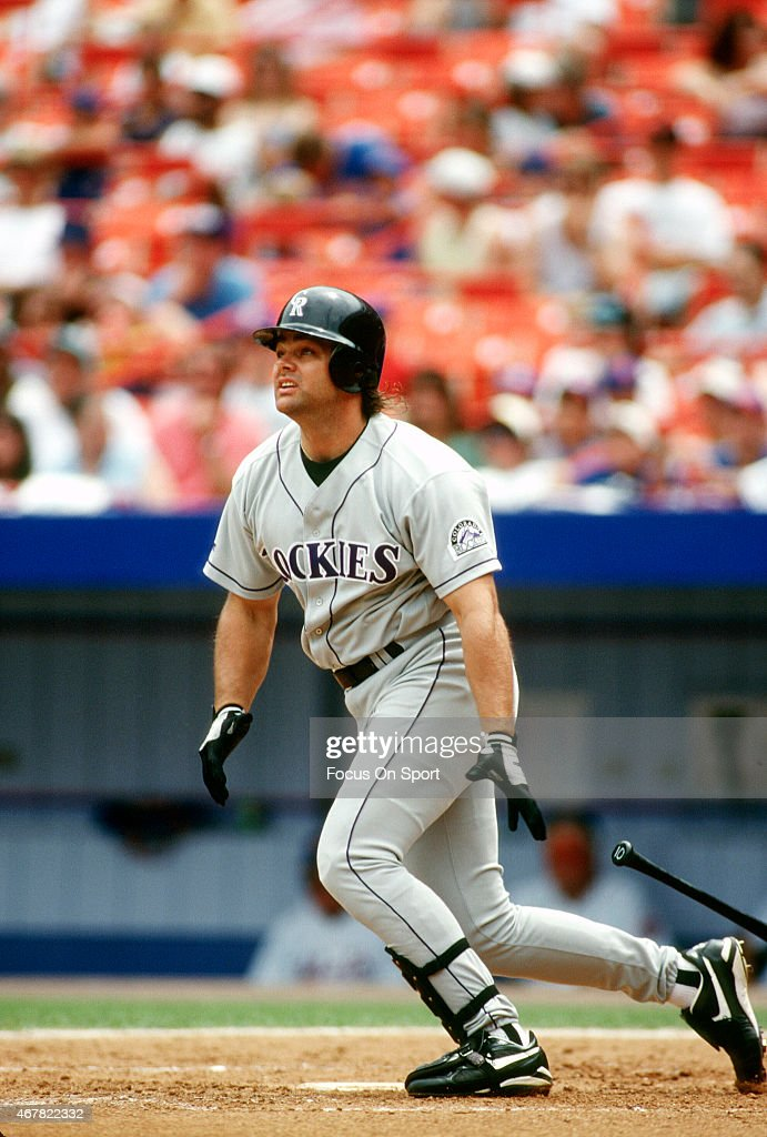 Dante Bichette #10 of the Colorado Rockies swings and watches the flight of his ball against the New York Mets during an Major League Baseball game circa 1995 at Shea Stadium in the Queens borough of New York City. Bichette played for the Rockies from 1993-99.