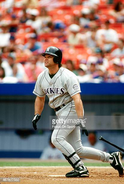 Dante Bichette of the Colorado Rockies swings and watches the flight of his ball against the New York Mets during an Major League Baseball game circa...