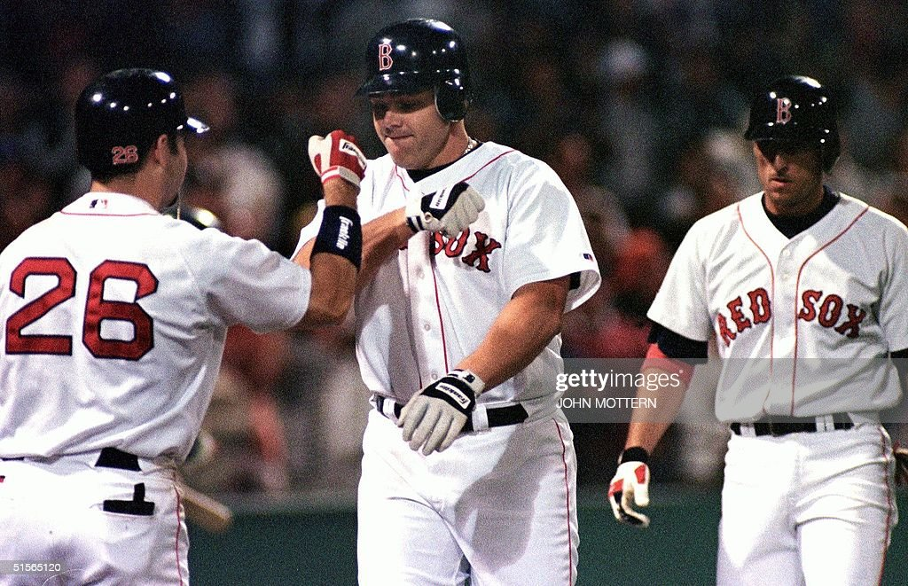 Dante Bichette (C), the Boston Red Sox designated hitter, is congratulated by Lou Merloni (L) after hitting a two-run home run in the 3rd inning bringing in Nomar Garciaparra (R) 19 September, 2000 at Fenway Park in Boston, Massachusetts.