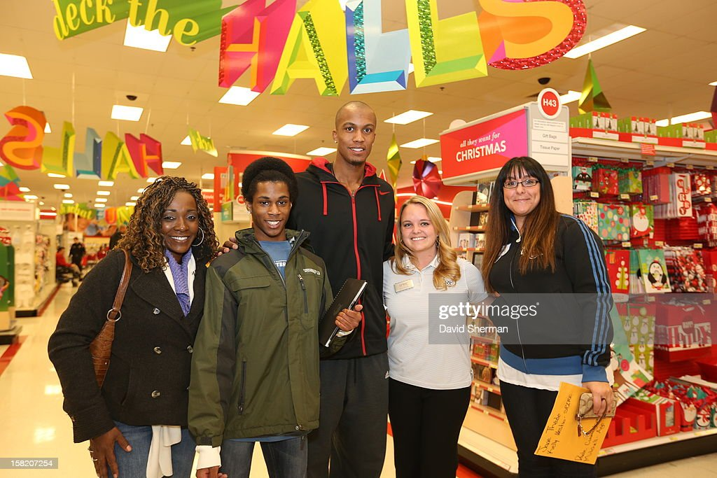 Dante Cunningham of the Minnesota Timberwolves pauses for a picture with Mitchell, who is up for adoption, and the team staff and sponsors that will help with the surprise $1,000 shopping spree on December 10, 2012 at Target in Minneapolis, Minnesota.