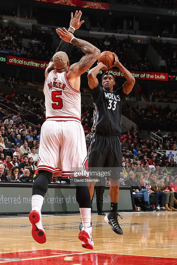 Dante Cunningham #33 of the Minnesota Timberwolves shoots against Carlos Boozer #5 of the Chicago Bulls on January 27, 2014 at the United Center in Chicago, Illinois.