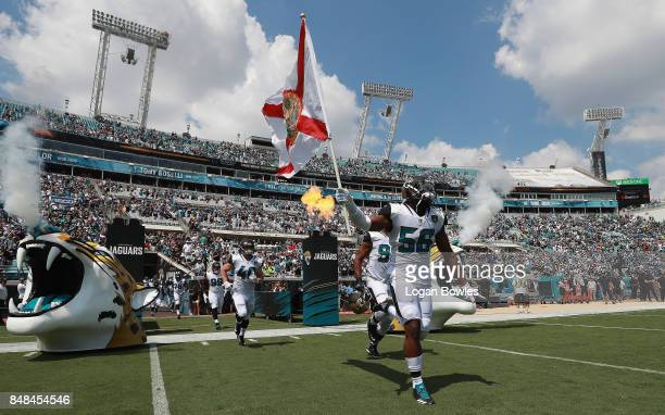 Dante Fowler of the Jacksonville Jaguars takes the field with his teammates and a Florida state flag prior to the start of their game against the...