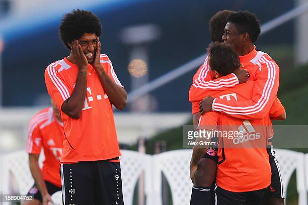 Dante laughs with Rafinha and David Alaba during a Bayern Muenchen training session at the ASPIRE Academy for Sports Excellence on January 3 2013 in...