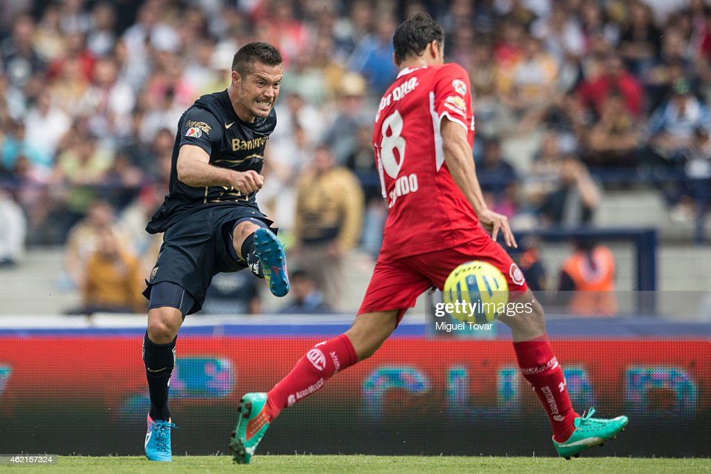 Dante Lopez of Pumas kicks the ball as Aaron Galindo tries to block of Toluca defends during a match between Pumas UNAM and Toluca as part of 3rd round Clausura 2015 Liga MX at Olympic Stadium on January 25, 2015 in Mexico City, Mexico.