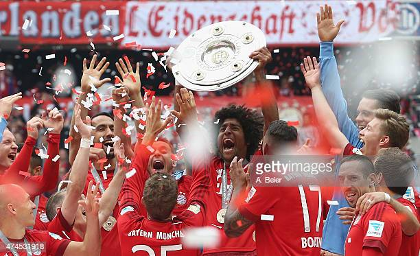Dante of Bayern Muenchen lifts the Bundesliga trophy to celebrate winning the German Championship after the Bundesliga match between FC Bayern...