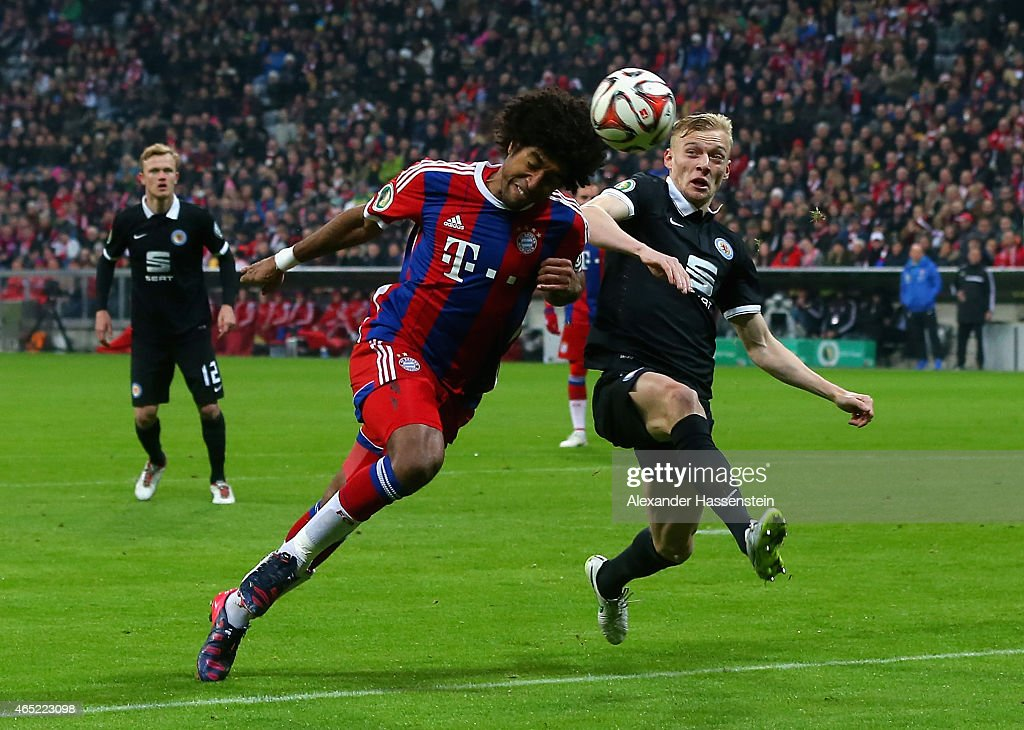 Dante of FC Bayern Muenchen heads the ball under the pressure of Maximilian Sauer of Eintracht Braunschweig during the round of 16 DFB Cup match between FC Bayern Muenchen and Eintracht Braunschweig at Allianz Arena on March 4, 2015 in Munich, Germany.