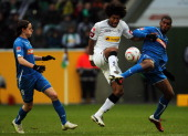 Dante of Moenchengladbach is challenged by Sebastian Rudy and Ryan Babel of Hoffenheim during the Bundesliga match between Borussia Moenchengladbach...