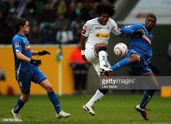 Dante of Moenchengladbach is challenged by Sebastian Rudy and Ryan Babel of Hoffenheim during the Bundesliga match between Borussia Moenchengladbach...