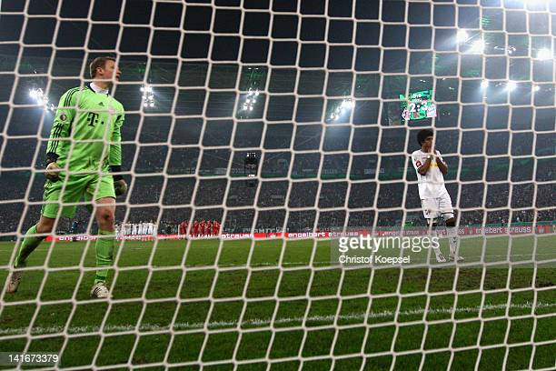 Dante of Moenchengladbach looks dejected after missing a penalty against Manuel Neuer of Bayern during the penalty shootout during the DFB Cup semi...