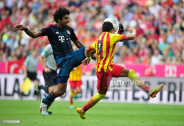 Dante of Muenchen challenges Alexis Sanchez of Barcelona during the Uli Hoeness Cup match between FC Bayern Muenchen and FC Barcelona at Allianz...