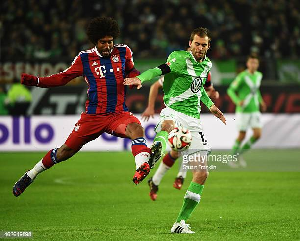 Dante of Muenchen is challenged by Bas Dost of Wolfsburg during the Bundesliga match between VfL Wolfsburg and FC Bayern Muenchen at Volkswagen Arena...