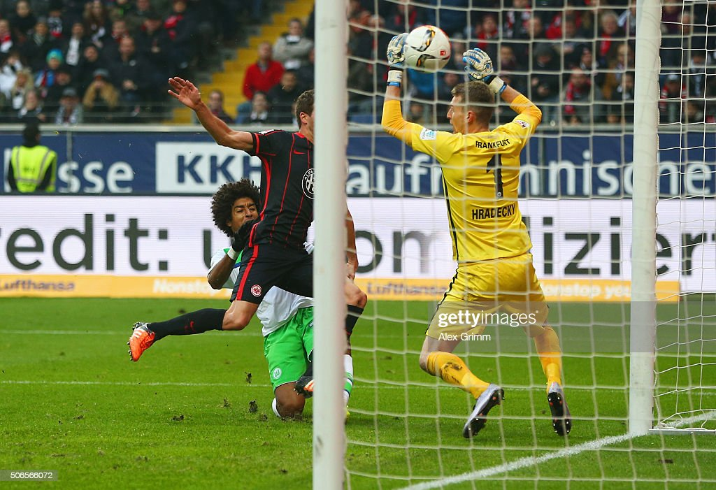 Dante of VfL Wolfsburg (L) beats David Abraham of Eintracht Frankfurt to score their first goal past goalkeeper Lukas Hradecky of Eintracht Frankfurt during the Bundesliga match between Eintracht Frankfurt and VfL Wolfsburg at Commerzbank-Arena on January 24, 2016 in Frankfurt am Main, Germany.