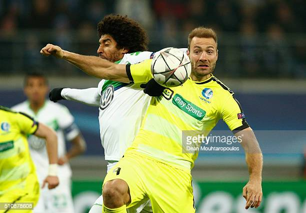 Dante of Wolfsburg and Laurent Depoitre of KAA Gent compete for the ball during the UEFA Champions League round of 16 first leg match between KAA...