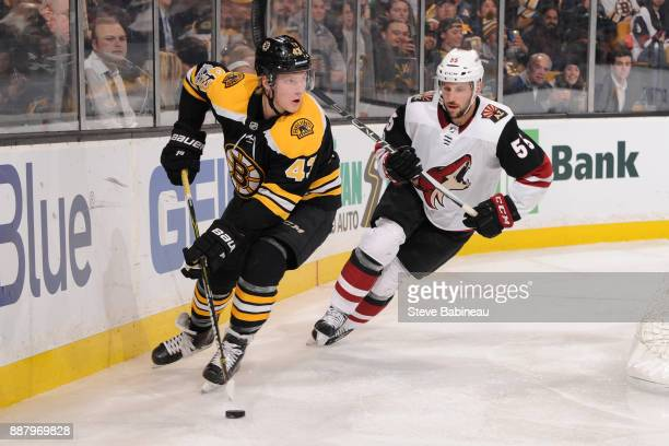Danton Heinen of the Boston Bruins skates with the puck against Jason Demers of the Arizona Coyotes at the TD Garden on December 7 2017 in Boston...