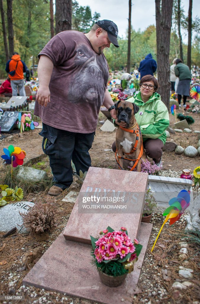 Danuta (R) and Tomir (L) visit with their bulldog Buster the grave of their late bulldog Prymus at the pet cemetary in Nowy Konik, near Warsaw, on October 7, 2012 on the annual meeting for owners of late pets. The holiday is organized every year on first sunday in October on the model of very popular in Poland All Saints day (November 1) and gather hundreds of people wishing to light a candle for their pets.
