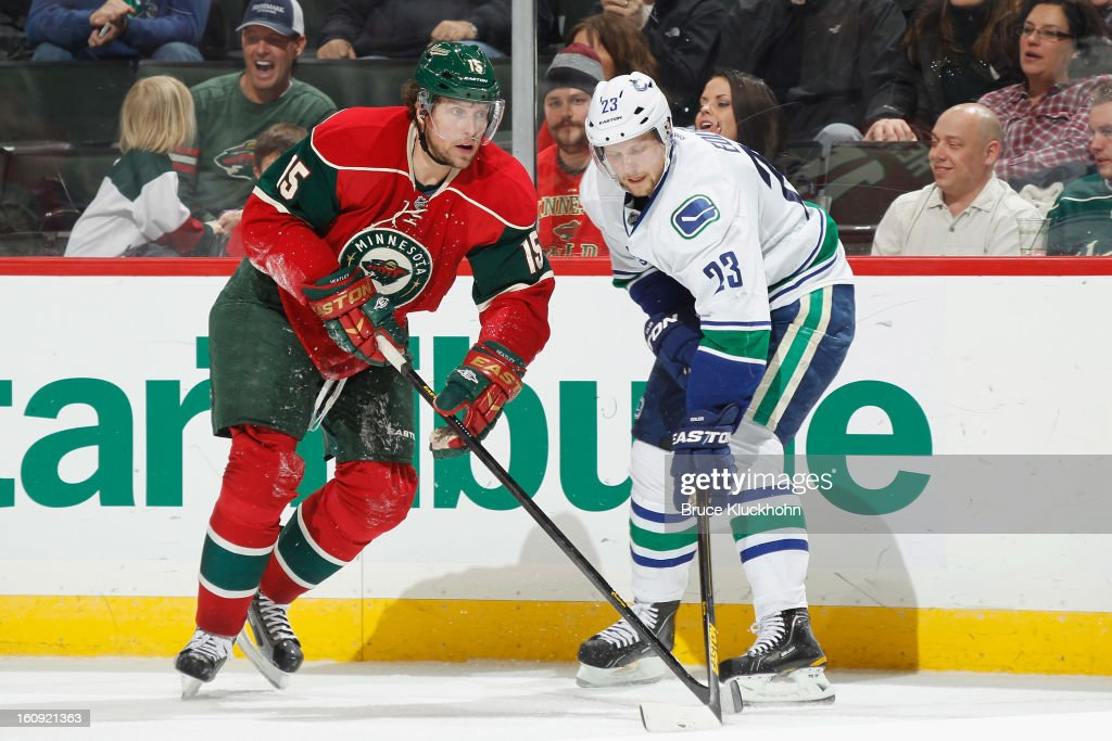Dany Heatley #15 of the Minnesota Wild and Alexander Edler #23 of the Vancouver Canucks battle for control of the puck during the game on February 7, 2013 at the Xcel Energy Center in St. Paul, Minnesota.