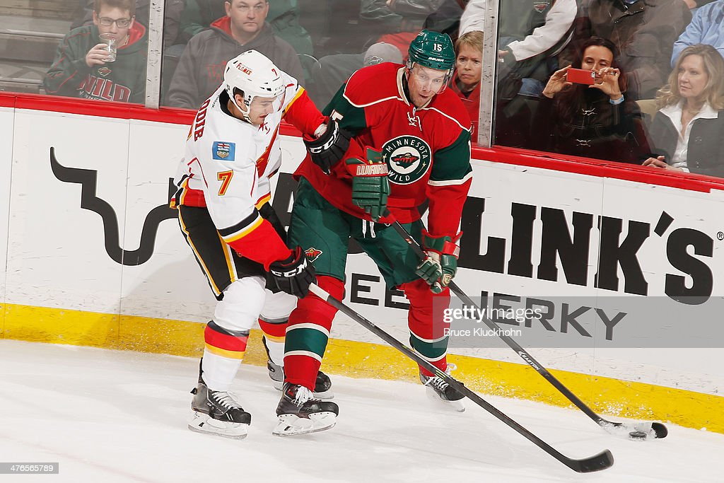 Dany Heatley #15 of the Minnesota Wild controls the puck against T.J. Brodie #7 of the Calgary Flames during the game on March 3, 2014 at the Xcel Energy Center in St. Paul, Minnesota.