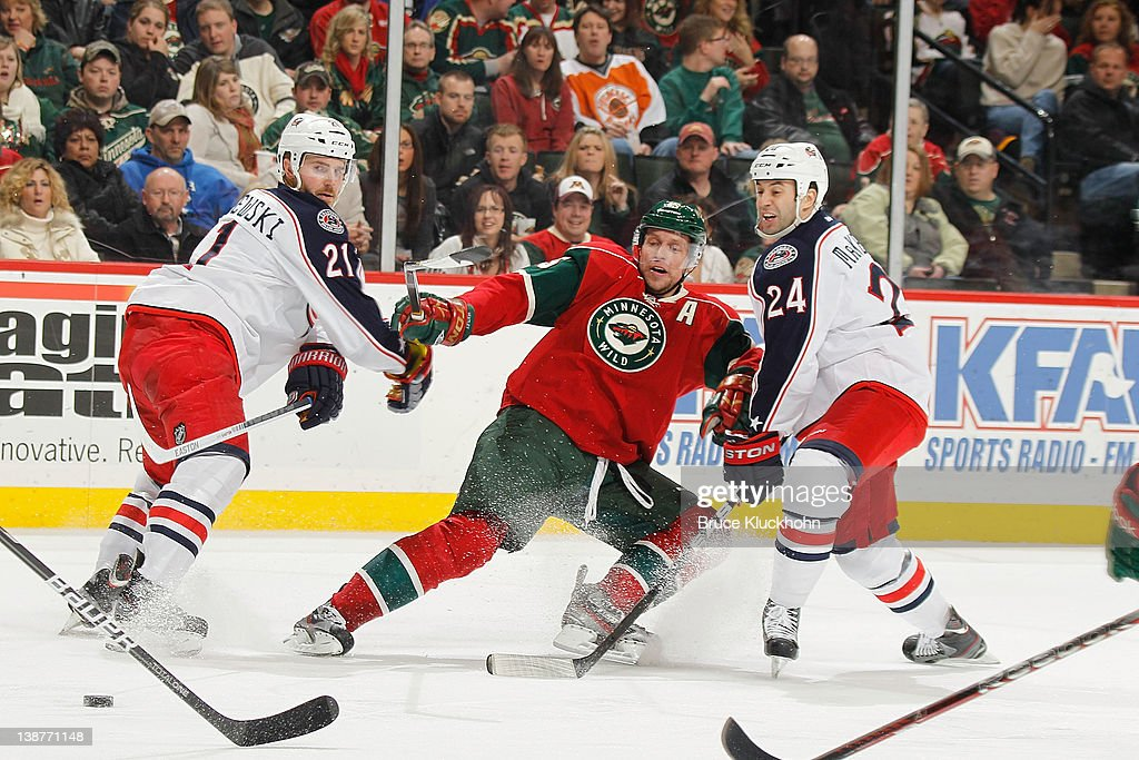 <a gi-track='captionPersonalityLinkClicked' href=/galleries/search?phrase=Dany+Heatley&family=editorial&specificpeople=202142 ng-click='$event.stopPropagation()'>Dany Heatley</a> #15 of the Minnesota Wild loses his balance while being defended by (L-R) <a gi-track='captionPersonalityLinkClicked' href=/galleries/search?phrase=James+Wisniewski&family=editorial&specificpeople=688111 ng-click='$event.stopPropagation()'>James Wisniewski</a> #21 and <a gi-track='captionPersonalityLinkClicked' href=/galleries/search?phrase=Derek+MacKenzie&family=editorial&specificpeople=685877 ng-click='$event.stopPropagation()'>Derek MacKenzie</a> #24 of the Columbus Blue Jackets during the game at the Xcel Energy Center on February 11, 2012 in St. Paul, Minnesota.