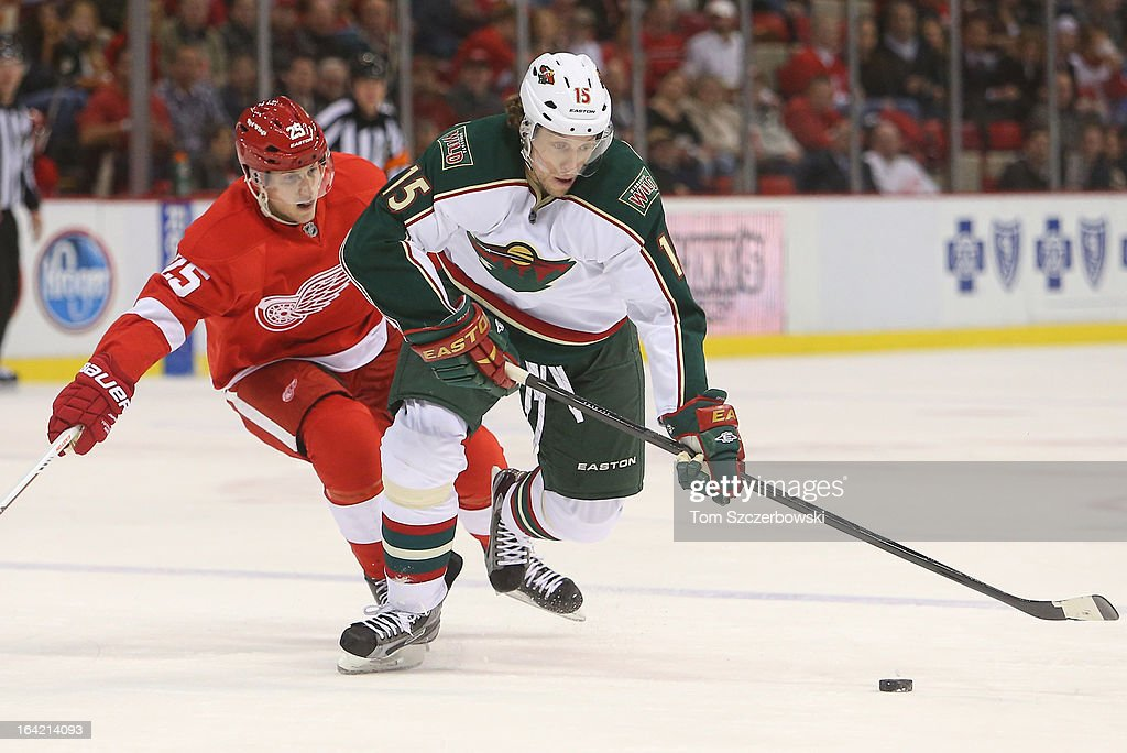 Dany Heatley #15 of the Minnesota Wild skates with the puck during their NHL game as Cory Emmerton #25 of the Detroit Red Wings applies pressure at Joe Louis Arena on March 20, 2013 in Detroit, Michigan.