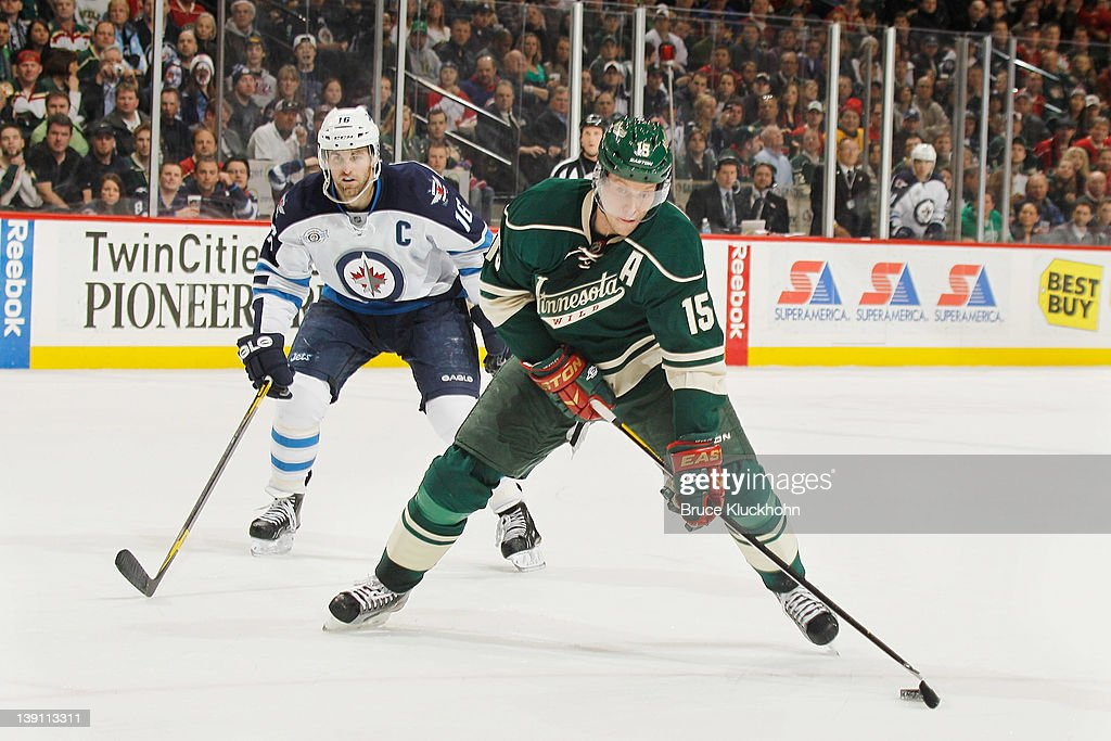 <a gi-track='captionPersonalityLinkClicked' href=/galleries/search?phrase=Dany+Heatley&family=editorial&specificpeople=202142 ng-click='$event.stopPropagation()'>Dany Heatley</a> #15 of the Minnesota Wild skates with the puck with <a gi-track='captionPersonalityLinkClicked' href=/galleries/search?phrase=Andrew+Ladd&family=editorial&specificpeople=228452 ng-click='$event.stopPropagation()'>Andrew Ladd</a> #16 of the Winnipeg Jets defending during the game at the Xcel Energy Center on February 16, 2012 in St. Paul, Minnesota.