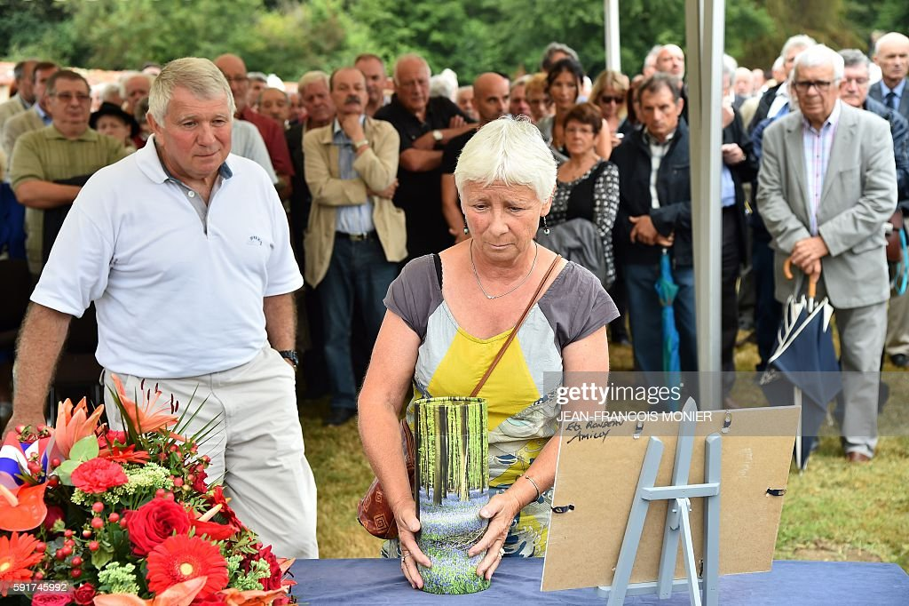 Dany Seguy followed by her brother Michel Seguy displays the urn during the funeral of their father Georges Seguy former secretary general of French...