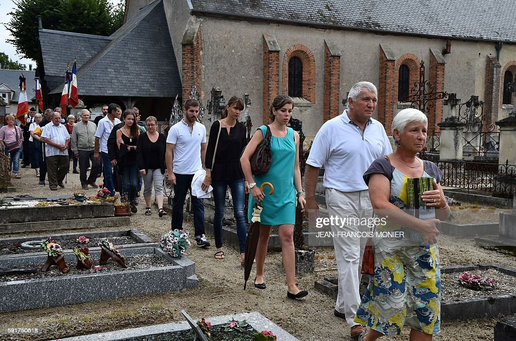 Dany Seguy followed by her brother Michel Seguy relatives and officials carries the funerary urn of her father Georges Seguy former secretary general...