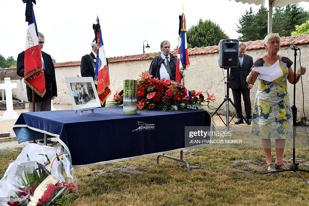 Dany Seguy reads a poem of Paul Eluard as she stands next to the urn during the funeral of her father Georges Seguy former secretary general of...
