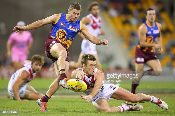 Danye Zorko of the Lions has his kick smothered by Luke Parker of the Swans during the round seven AFL match between the Brisbane Lions and the...