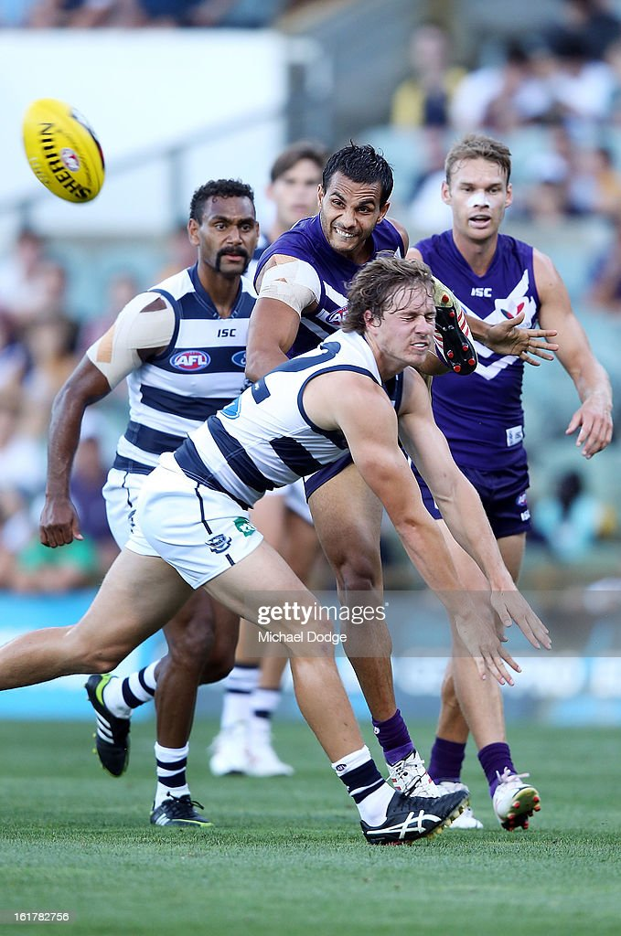 Danyle Pearce of the Fremantle Dockers kicks the ball past Mitch Duncan of the Geelong Cats during the round one NAB Cup AFL match between the Fremantle Dockers and the Geelong Cats at Patersons Stadium on February 16, 2013 in Perth, Australia.