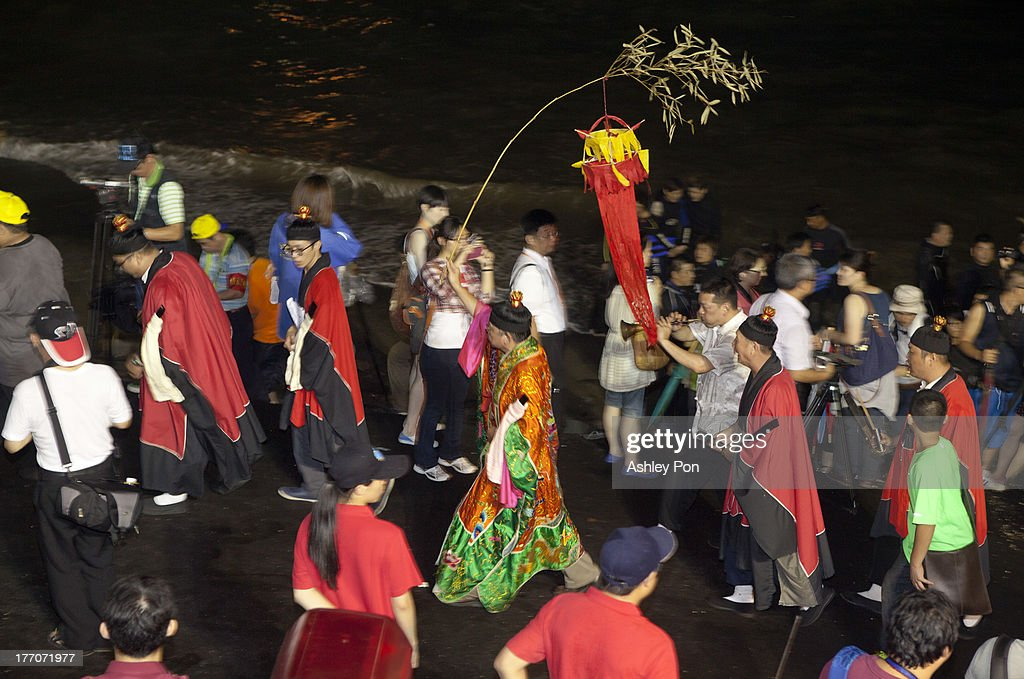 A Daoist ritual master leads a ceremony to beckon the spirits of the dead before releasing water lanterns into the sea to celebrate the mid-summer Ghost Month Festival on August 20, 2013 in Keelung, Taiwan. Paper houses are burnt at sea to retrieve ghosts and lonely spirits of underworld through waterways leading back to the land as part of a Pudu (universal salvation) ritual. On the 14th day of the 7th lunar month, the gates of the underworld are opened for the spirits of the departed to come back to the land for a month long period of universal salvation in the land of the living.